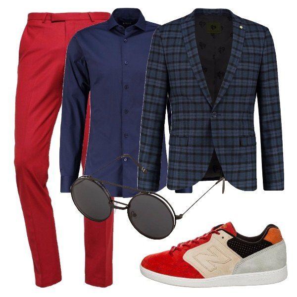 Per un uomo a cui piace la moda e vuole portarla in ufficio. Pantaloni rossi eleganti, camicia blu, giacca a quadri, sneakers basse multicolore e occhiali da sole neri con lenti tonde.
