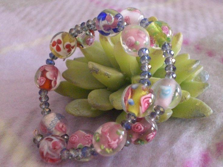 Bracciale creato su filo armonico, rondelle di cristallo color grigio-azzurro e perle in vetro decorate con motivi floreali vari. ( 10,00 ) https://www.facebook.com/argentea.fantasia