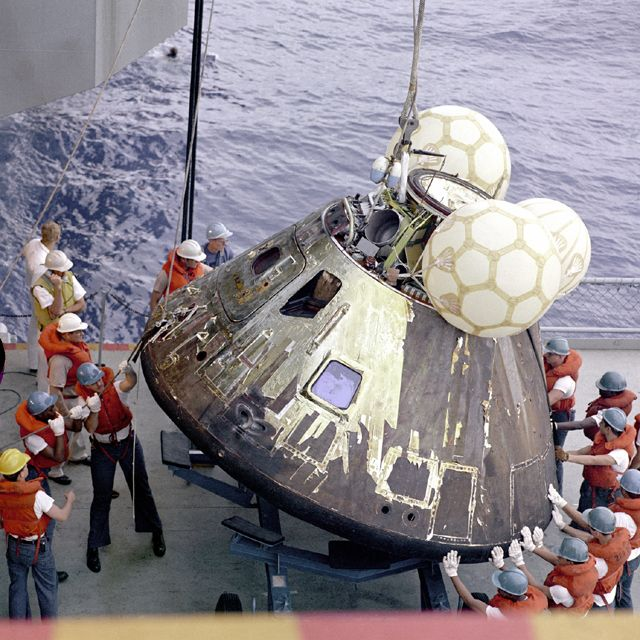 The prime recovery ship for the Apollo 13 mission hoists the Command Module aboard the ship.
