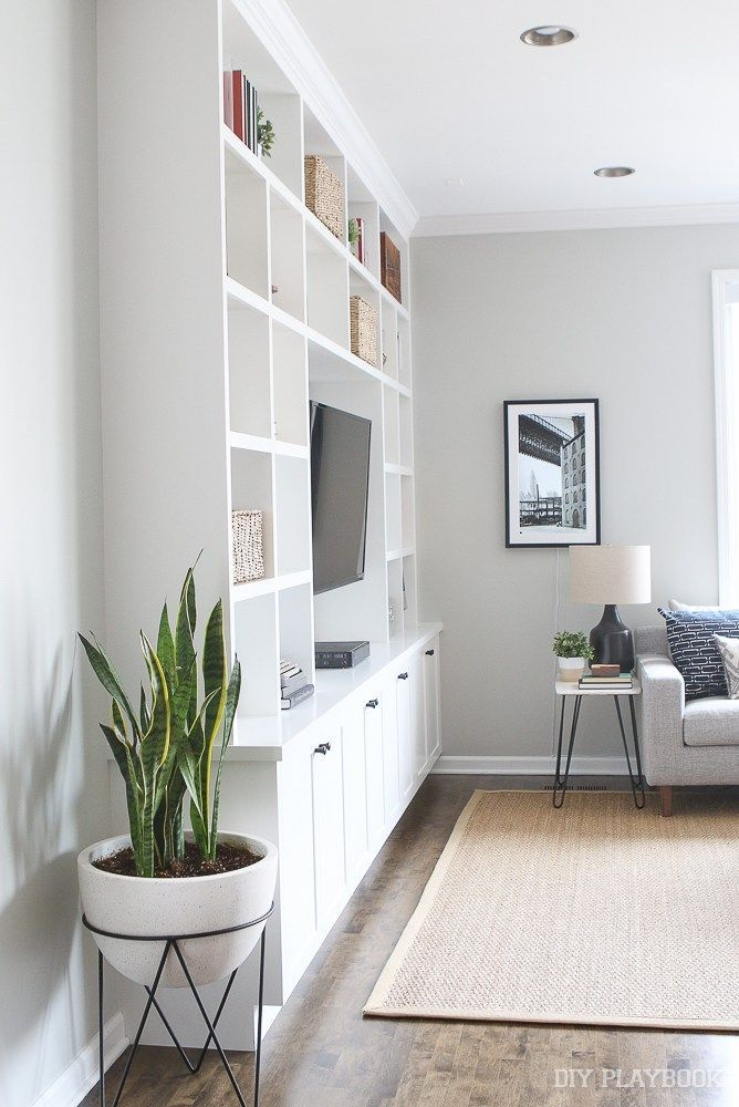 Love these built-ins in this family room. Plus the cute marble side table, with the lamp and art, make a cozy corner in this space.