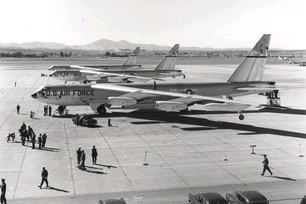 Black-and-white photo of three B-52s parked close together facing left, as personnel on the ground prepare them for departure