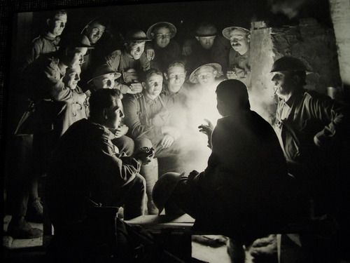 Soldiers of the 1st Australian Divison tell stories by lamplight. Ypres, 1917.   Frank Hurley