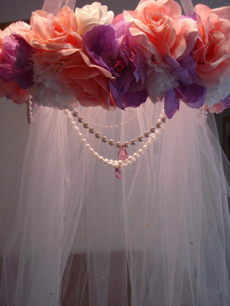 DIY bed canopy from tulle, fake flowers, dollar store pearl necklaces.  I made this one.. not too bad if I do say so myself! You can now find TUTORIAL ADDED to my blog!