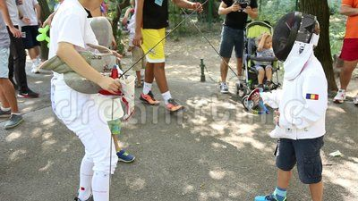 Children on fencing training - children in costumes fencing.