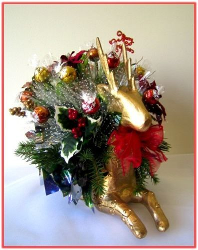 """""""GOLDEN REINDEER"""" Candy Bouquet : Our Golden Reindeer is carrying a   gorgeous Candy Bouquet sure to please anyone who loves the taste of fine Lindt chocolates. This Candy Bouquet is made of 15pcs Lindt truffles combined with silk flowers, greenery and colourful cellophane.    Price as shown AUD $45.95    Code: CB 0342"""
