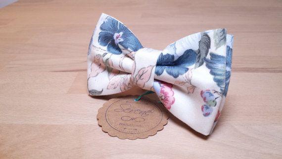 Papillon ideato e confezionato con passione e attenzione ai dettagli, fatto a mano con tanto amore in Italia!  Papillon bianco a fiori azzurro e rosa - Tessuto: Cotone - Dimensioni fiocco: 11,5 cm x 6,5 cm.  MODELLI: - SELF TIE: Il modello self tie è il vero e originale papillon, ha un tocco particolare e di carattere ed è più movimentato del modello pretied. (verrà spedito già annodato per vostra praticità, inoltre ha cinturino regolabile con gancetti, così che non si è obbligati a fare il…