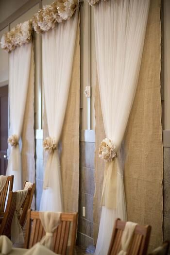 Burlap and tulle window covers with rosettes. Done with coral and ivory flowers, this would be easy, cheap, and help cover windows if the reception space is too bright!