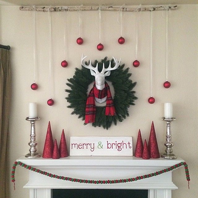 Can't go wrong with a festive wreath to frame a faux deer head. We love how this maxxinista added candlesticks and garland for a little extra detail.