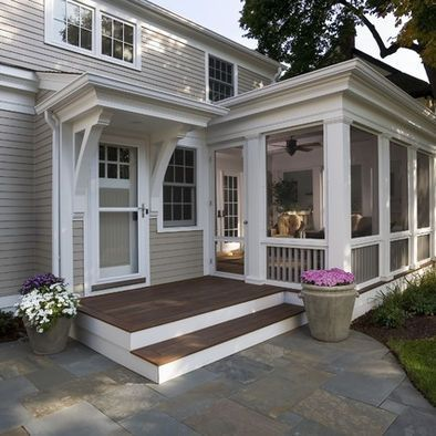 """Back Entry. Large steps and landing are welcoming and easy to navigate. Dark porch floor ads contrast. Screened in porch with separate entry gives """"peek"""" into home and gives relaxed appearance. Potted flowers are easier to manage. Shade trees and door awning. Multi sized stone/paver patio ads texture and greys and blues. Clean bracket and molding detail are ornate but not fussy."""