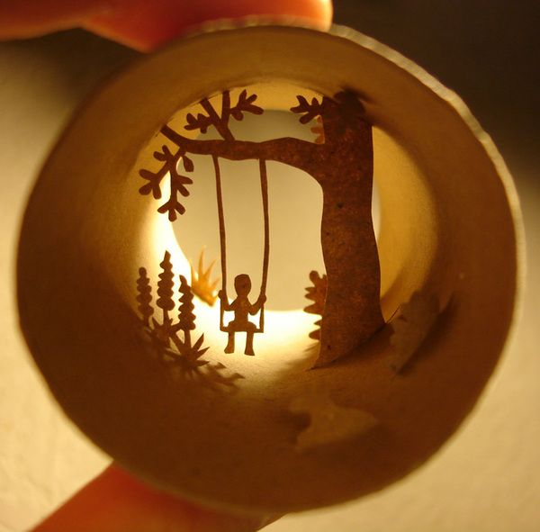 Swing Collage, paper cut  This miniature is all within a toilet paper roll. His site has tons of these little masterpieces.