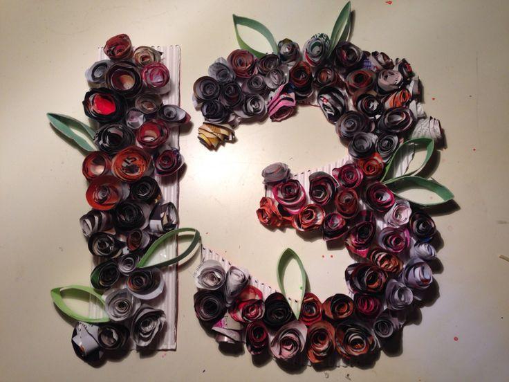 Mainoslehdistä tehtyjä kukkia, joita vähän vesiväreillä maalattu. Liimattu pahville. Lehdet tehty talouspaperirullasta.