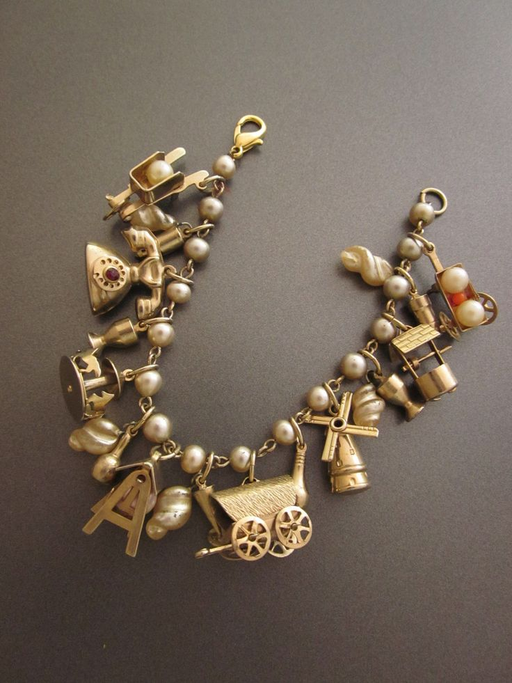 charming vintage bracelet holds many charms on a pearl and gold tone metal chain
