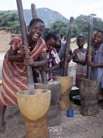 African girls pounding maize for flour.