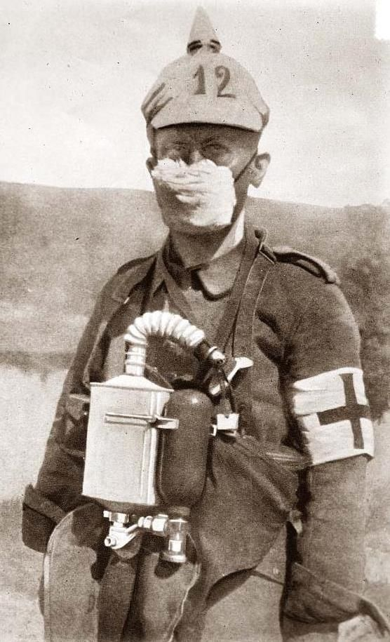 "German medic wearing an early-WWI gas mask.  The first ""masks"" to protect against the deadly gasses, such as chlorine, were nothing more than dampened cloth over the nose & mouth. It was believed that dampening the cloth with concentrated urine was more effective than water.  GROSS!"