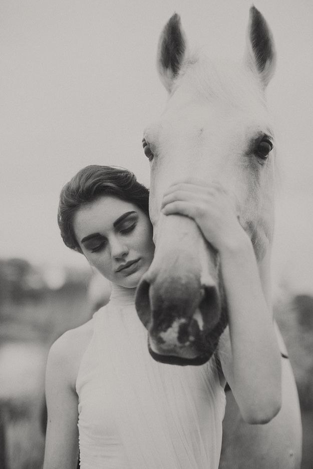Romantic horse photography of woman in white dress, holding face of beautiful horse with white, grey color and pretty face. They look marvelous.