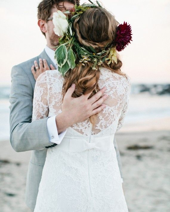 Post-ceremony, this bride dressed up her braided half-up-half-down hairstyle with a flower crown that coordinated with her bouquet, a cascading arrangement of vibernum berry, tuberose, dahlias, figs, variegated tree ivy, roses, pepper berry, scented geranium, and blushing bride.