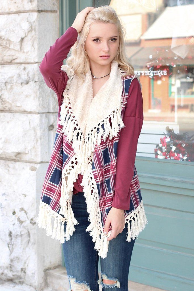 This open style plaid print vest features frayed tassels all along the hemline and a faux fur lining that is exposed in the front. Navy, red, and cream in color with cream colored fur.
