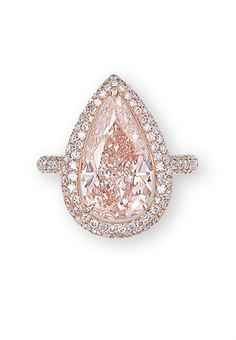 A COLOURED DIAMOND AND DIAMOND RING Set with a pear-shaped fancy orangy pink diamond weighing 5.45 carats, within a pavé-set brilliant-cut diamond surround and half-hoop, mounted in 18k rose gold