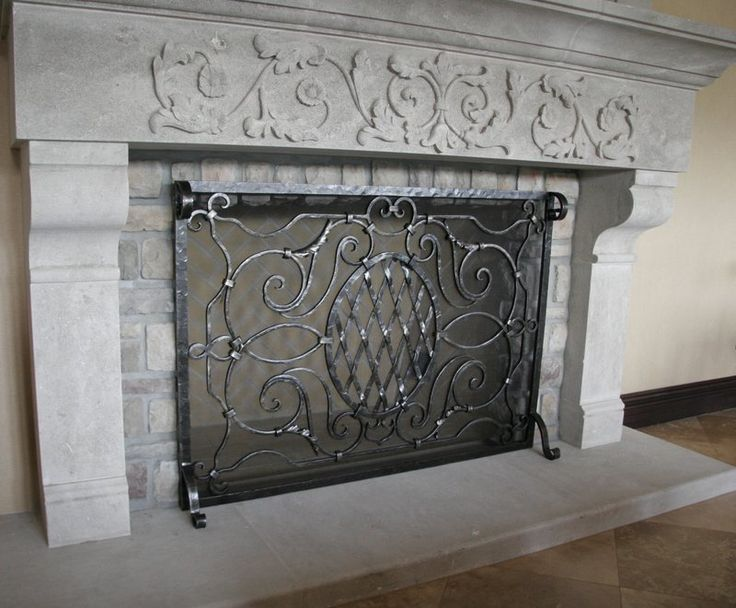 Single panel fireplace screen features ornate detail and an oval lattice shape that compliments the custom fireplace details.  Custom built by Noble Forge, artisan blacksmith in North Hollywood.