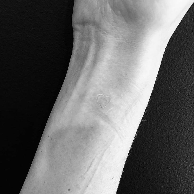 White ink heart tattoo on the inner wrist.
