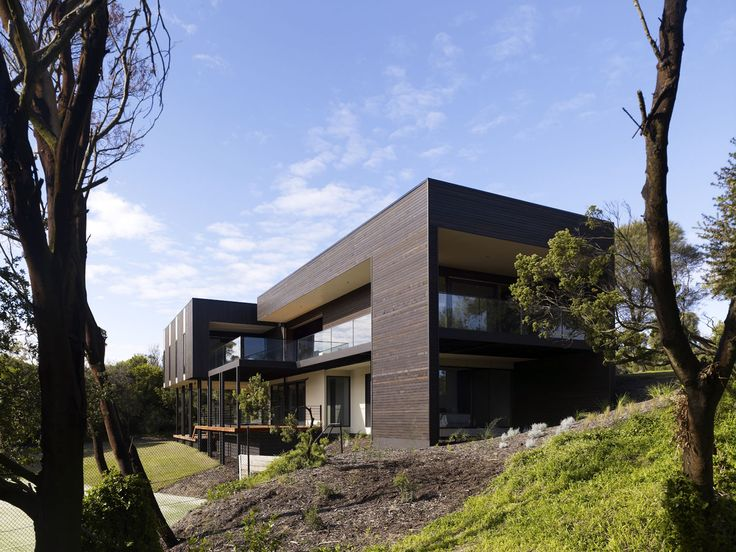 A sophisticated home on a golf course featuring a tennis court, hardwood floors, concrete walls