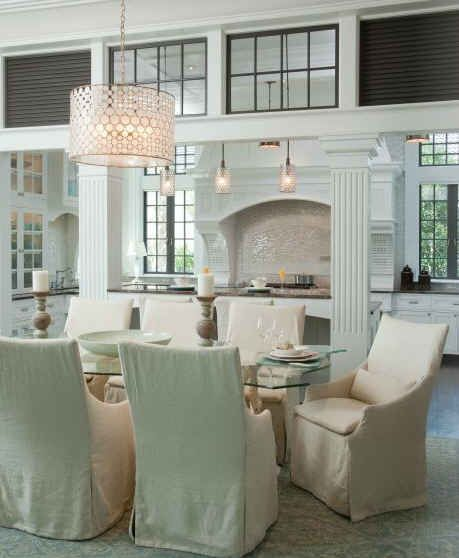 Pale, slipcovered chairs around the dining room table epitomize easy, beachy chic.