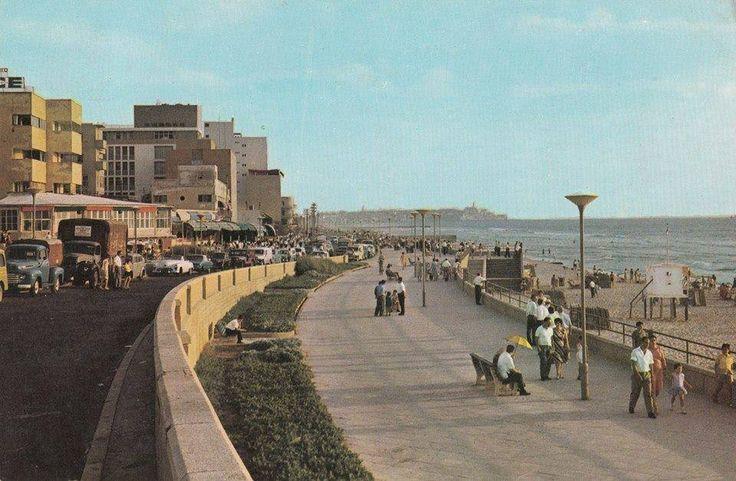 """משפחות מטיילות ומעבירות את הערב בטיילת, משמאל נראים """"קפה פילץ"""" ו""""קפה גינתי ים"""". תל אביב 1965-6."""