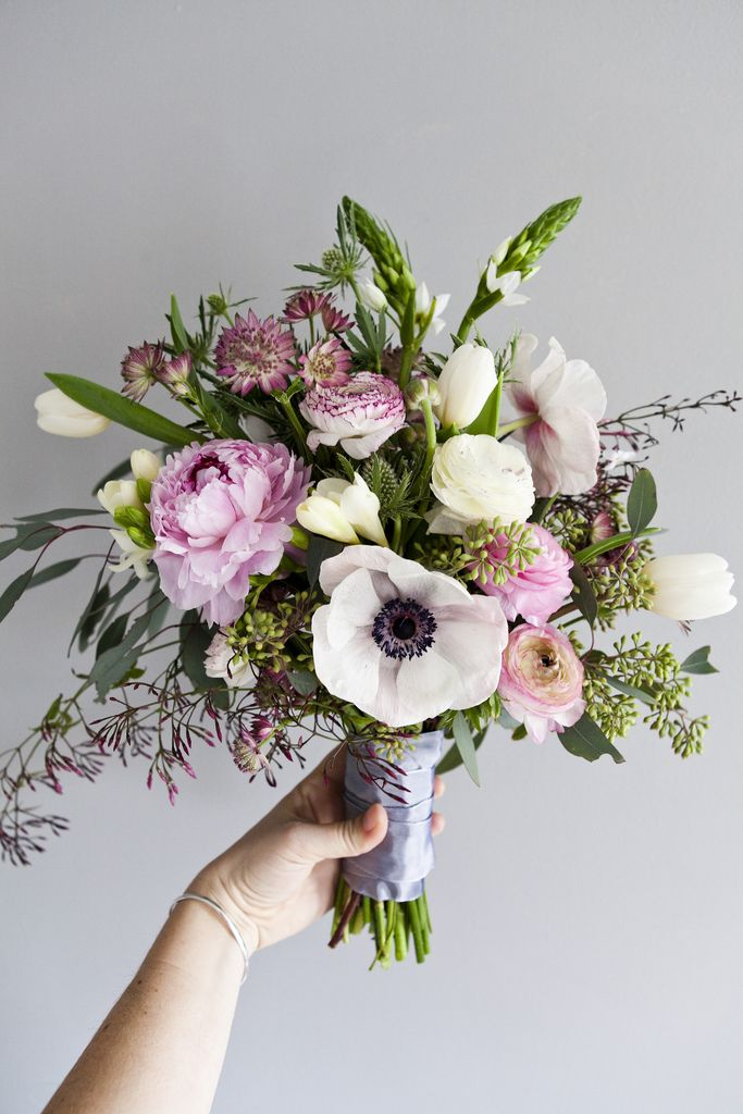Beautiful bouquet with peonies, ranunculus, Star of Bethlehem, freesia, small filler flowers, and greenery.