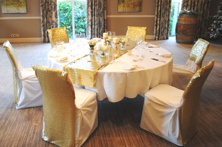 Gold sequined chair veils on white cotton chair covers with matching table runners at The Vineyard, Stockcross by Simply Bows and Chair Covers