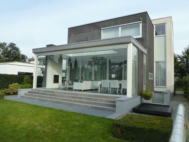 Een glazen schuifwand maakt van een overkapping een tuinkamer. Deze kleine aanpassing levert enorm veel plezier op!