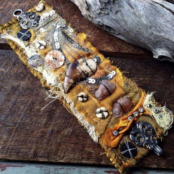 Un textil gloriosamente shabby y andrajosa rústico tribal brazalete en tonos de amarillo oro. Reciclado sari de seda adornados con garra de hueso tallado, sunstone crudo, fragmento de sari bordada vintage, raído terciopelo amarillo, botones y abalorios.  Cosido a mano y reconstruye capa usando a telas rescatadas y recuperadas. Creado para ver maltratadas y audaz.  Se cierra con un broche de la capa de salvado. El brazalete es un pelín más 7 1/2 pulgadas (19 cm) de gancho al ojo.  Para más…