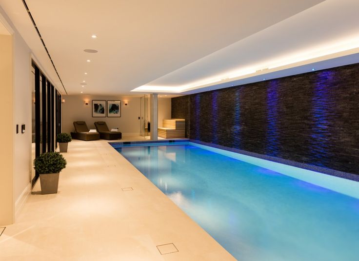 The wall lights in the lounging area of this pool room are specially water tight as required for rooms containing water.  The coffered ceiling is lit with LED ribbon for glare-free lighting.  Colour changing LED ceiling downlights feature the textured back wall of the pool room.