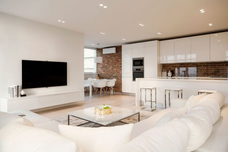 Beautiful Open Floor Living Space from White Loft In Kiev Designed By Kashuk Constantine showing Living Room and Kitchen and Dining Area with Modern White Cabinets and Wall Mounted TV and White Bench and Exposed Brick Wall Decor