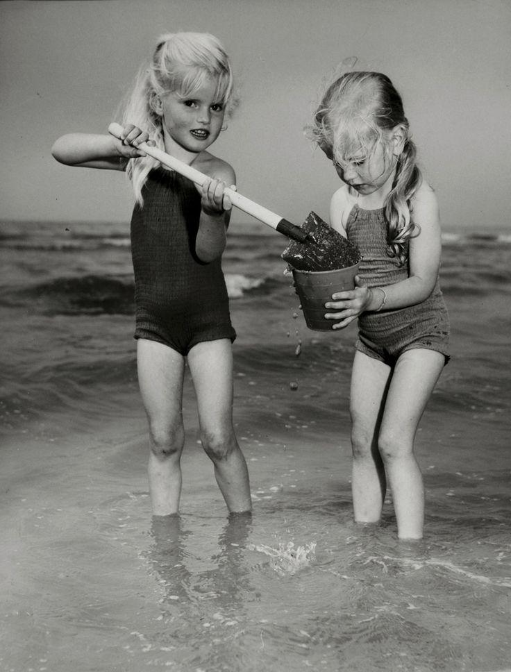 Meisje in badpak schept zand in emmertje dat het andere meisje vasthoudt.