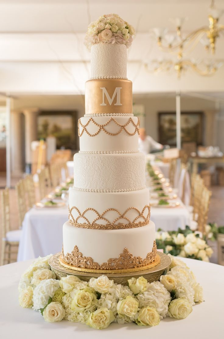 Gold and white lace wedding cake with live floral base and gold metallic. This custom 6 tier cake was created by taste of eden bakery. I wanted to Combine Metallica With lace and white pretty delicate textures plus a floral base and topper and this was the final product which turned out amazing.