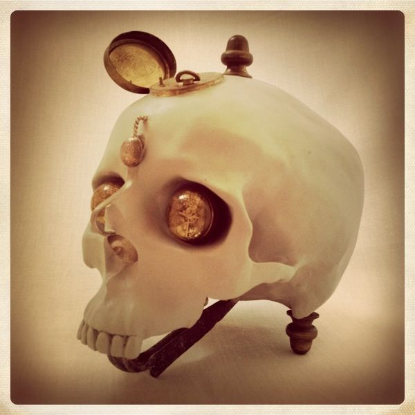 Ceramic skull, antique brass music box (plays Debussy - Claire de Lune) , resin eyes with old, nautical metal buttons, old abbatoir hook and brass leg stand - handmade by TheBlackEnglishman