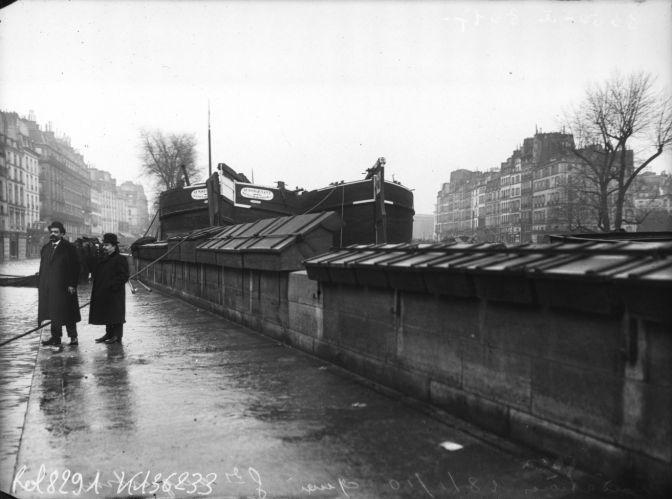 Inondations, 28/01/1910, quai des Grands-Augustins (les péniches surplombent les boîtes des bouquinistes, Paris, 6e arrondissement). Photographie de presse : Agence Rol