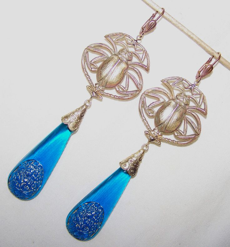 Vintage Czech dangle earrings with scarab and floral blue glass drops.