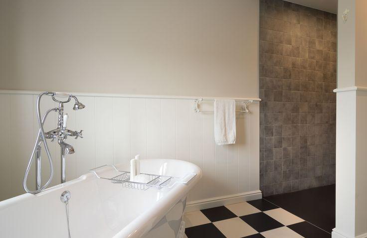 Houten lambrisering rondom in de badkamer. Vloer in dambord patroon. Bad in Engelse stijl.