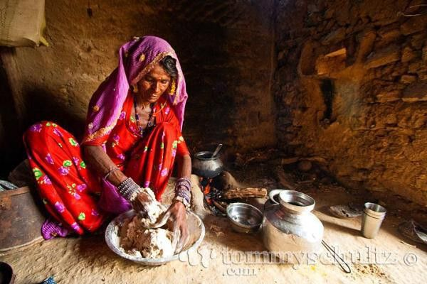 Rajasthani woman in a red sari making dough for chapati bread in Jaisalmer