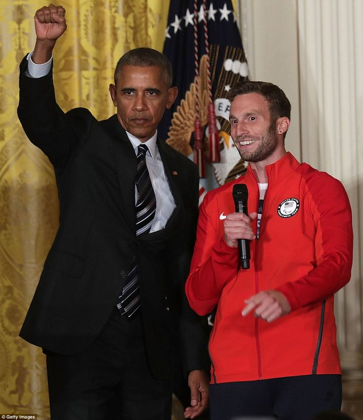 President Obama stands on stage withParalympic soccer player Josh Brunais during the event in the East Room of the White House