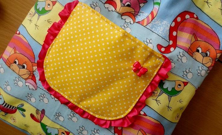 Kočičí kamarádi... Malá taštička pro děti, je ušita z české bavlněné látky. Na přední straně je malá kapsička, jejíž obvod zdobí volánek z růžové stužky a mašlička (knoflík) stejné barvy. Rozměr: š. 27 cm (v horní části 24 cm) v. 28 cm hloubka 5 cm Velikost kapsičky 10 x 12 cm. Kabelka má podšívku - bílá látka s modrými puntíky (100% česká bavlna) ...