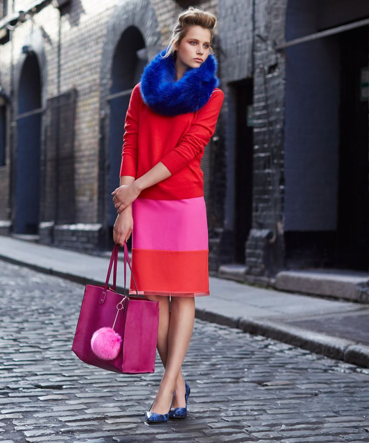 Knitted red jumper and fitted skirt, paired with blue faux-fur circle scarf and large shopper bag, all Savida by Dunnes Stores