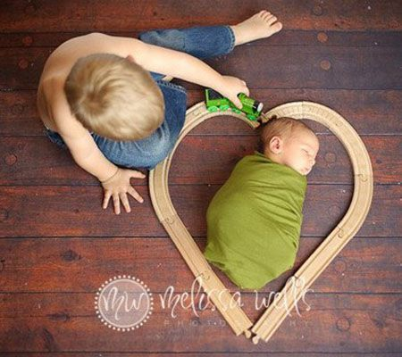 Sibling – All Aboard , Use train tracks to build a heart around your swaddled baby. Let big brother or sister drive the train around it to c...