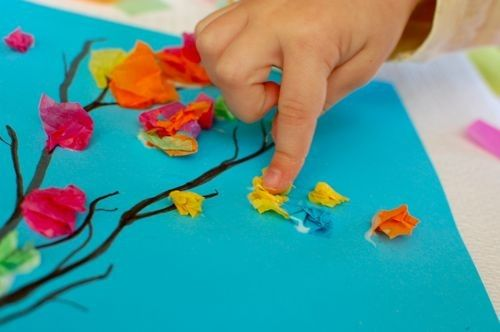 find a real (thin) twig or branch you like and hot glue it to a colorful background then start adding the colorful flowers. Children could do this without the hit glue.