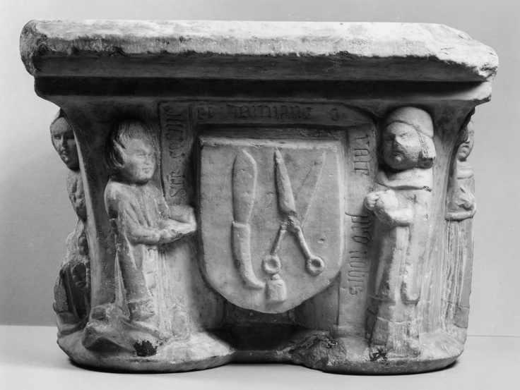 """Cosmas and Damian are depicted as supporters of the arms of the guild of barber-surgeons carved into a capital, 15th century, from the Carmes monastery in Trie-sur-Baïse in southwestern France. The inscription reads, """"Saints Cosmas and Damian pray for us""""."""