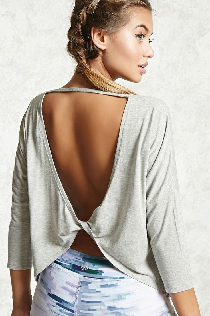 A soft knit active pullover top featuring a round neckline, a twisted back hem with an open-back cutout design, dropped shoulders with 3/4 sleeves, a high-low hem, and a flowy silhouette.