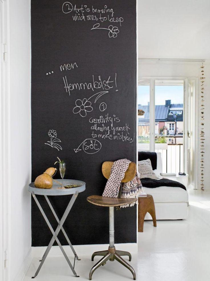 TØFT MED TAVLEMALING: En vegg i gangen er malt med tavlemaling. Det er en røff kontrast til den ellers hvite leiligheten.