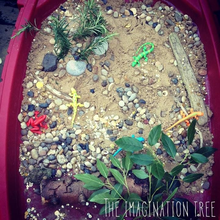 """Invitation to play at the sensory table from The Imagination Tree - sand, pebbles, driftwood, sticks, sequins, lizards, rosemary sprigs & leaves ("""",)"""