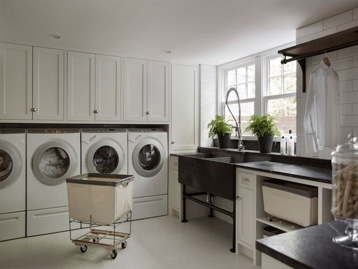 Amazing laundry room features white cabinets paired with black countertops and ceiling height subway tile backsplash. Laundry room with metal dual washstand next to built-in cabinets filled with linen laundry sorter bins as well under wall-mounted clothes rod, Basement laundry room with wall of cabinets over two sets of front load washers and dryers.